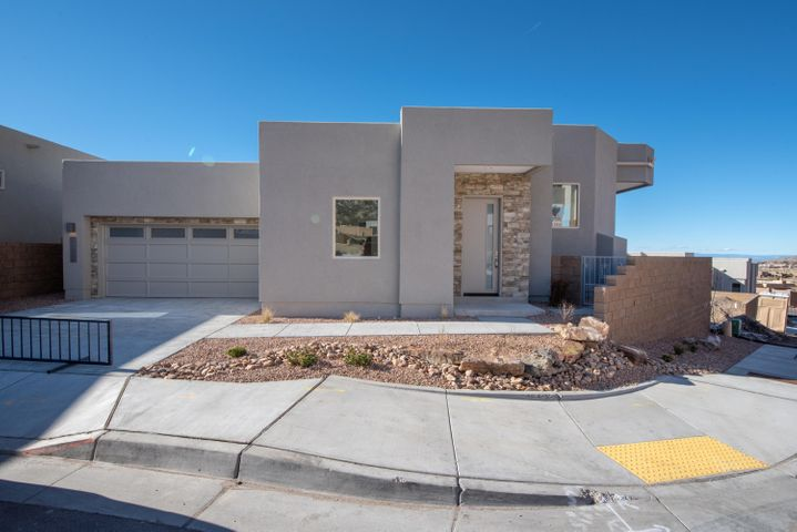 This newly completed Scott Patrick Custom Home is located in the Wilderness Canon Subdivision in High Desert.  Canon is a gated community situated on one of the highest points in High Desert.  This custom contemporary home includes some of the following features; granite and quartz countertops, wood flooring , carpet in bedrooms, tile flooring in bathrooms, walk in pantry with cabinet and countertop, stainless steel appliances, custom fireplace, skylights throughout, dishwasher, range hood, free standing oven, rear and front porches with panoramic views of the surrounding area and Sandia Mountains, and front and side yard landscaping.