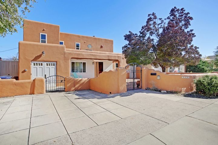 Amazing location just 2 blocks from UNM North Golf Course! Brick courtyard welcomes you into this 1950's charm with 2019 amenities. Living room has hardwood floors & cove ceilings. Kitchen has stainless steel appliances & 5 burner gas stove. Serene Mountain views from the kitchen sink opening to the back patio with built in hot tub. Upstairs master suite has views from the balcony & extraordinary walk in closet with laundry shoot. Master bath has privacy toilet & double sinks. Downstairs office could be used as 2nd living or dining room. Studio area/exercise room is heated. Updates include stucco, paint, & thermal windows. Lush backyard is meant for summer parties among the grapevines with a side entrance gate. Sprinkler system & insulated dog house. 19'x5' storage & storage in back.
