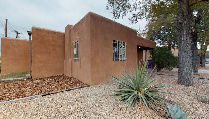 Attention Investors, Bargain Hunters, UNM parents! Just blocks from Nob HIll, UNM & UNMH with a WalkScore of 77, this great property includes a 3BR/2Full bath home + an attached 1 BR unit w/it's own kitchen and separate entrance! Surprisingly quiet inside in spite of busy corner lot! Freshly painted home features hardwood and tile flooring, cove ceilings, separated MBR w/it's own bath & large closet.+ huge utility room. Updates include: Furnace, cooler, bath vanity, kitchen w/gas range, fencing, tile surround in all baths, lighting, security bars, refreshed stucco, partial water & sewer lines.. Prior to listing, house rented for $1300/mo; apt $599/mo. Ample parking area includes large storage bldg and will easily accomodate 4 cars.