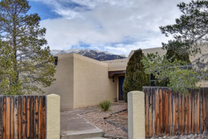 1st Showings, Open House, Sunday, 1-3 pm Dec 15th. How about a beautiful home for Christmas! Don't miss this character laden Sandia Heights Gem! Single story, great room open floor plan. Stunning mountain views, SO many windows, high ceilings, adobe walls, 2-way adobe fireplace w/ banco in great room and, spacious owner's suite with spacious walk-in closet, double sinks, whirlpool tub. Kitchen boasts lovely view of mountains from the sink, pantry and breakfast bar seats 5.  Nice sized secondary bedrooms share Jack 'n Jill bath. East facing backyard for cool shade on summer afternoons. Covered portal, patio and low maintenance backyard on corner lot with attached 2 car garage garage. Near Trader Joe's, many shops & services. Quick access to I-25 via Paseo del Norte or Tramway.