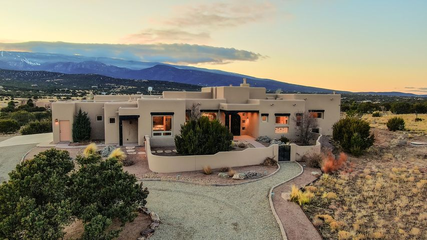 Incredibly stunning inside and out, this custom home is truly beautiful! It sits on 10 acres allowing for spectacular views of the Sandia Mountains and colorful sunsets in the evening. This resort like home was built in 2014 and boasts several high-end amenities like 2 master suites, radiant floor heating, refrigerated air, 2x6 construction, natural gas, 8ft solid interior doors, solar tubes, security system, huge 3 car garage with storage, and more. The artistic kitchen has Monogram Series stainless steel appliances, granite counter tops, and a lovely island with bar seating and breakfast nook. The spacious master has pocket doors allowing you to fully take in the views! It also has a huge bathroom and closet with double sinks and separate tub, shower. See amenities sheet for more