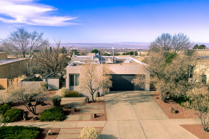 Incredible Modern Contemporary Home  Located At The Base Of The Sandia Mountains.Wow The  Views! Mountains In Front And City Off The Back Deck. This Home Has Many Updates And Improvements To Offer New Elastomeric Paint Outside, Custom Paint Inside, New Window Coverings, Gorgeous Flooring,  Updated Kitchen W/ Island, Gas Cooktop, Range Hood, Double Oven, Stainless Steel Appliances, And  Dinette Area. The Master Suite Is Located on The Main Floor W/ Walk in Closet. A Stylish Updated Master Bath Includes Double Vanities And Sinks, Separate Shower/ Tub And Modern Fixtures. Great For Entertaining Second Floor Has A  Large Family Room, Fireplace, Wet Bar And New Patio Doors To Access The Backyard.  Beautiful Xeriscaped Front Yard And Lawn Backyard. Schedule An Appointment Today For a Showing!