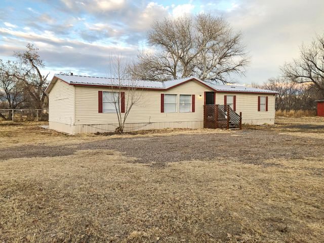 Check out this newly remodeled double wide on a 3/4 acre lot located in the heart of Los Lunas!  New metal roof, flooring, paint, blinds, fixtures and updated appliances installed in 2019. Master Cool AC unit.  Home has 4 bedrooms and 2 baths with a large concrete open patio in the backyard.  Storage building and completely fenced.