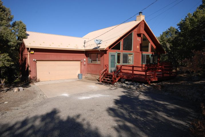 Cozy A-Frame on a wooded lot with paved access.  Two large bedrooms and 2 full  baths on main level.  Third bedroom is upstairs with private balcony.  Woodstove can heat the main rooms. A wall of glass brings the outside in.  Large deck wraps around 2 sides.  All electric on a private well. A sweet mountain home.