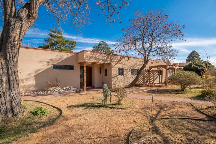 Charming territorial style home in the heart of Ridgecrest on over 1/4 acre bursting w/ roses, flowers & fruit trees, including apricot, cherry, plum, peach, apple & pomegranate. Remodeled in 2014 w/ open concept floor plan. Updates include granite counter tops, SS appliances, gorgeous wood windows, new electrical, new stucco & renovated bathrooms. New sewer line to street in 1/2020. Refrigerated air & new roof in 2015 w/ warranty. Light-filled separate apartment has spacious living room, bedroom, kitchen & washer/dryer -- perfect for guests, family or renters -- w/ separate garage bay. 3-car garage & ample outside space for RVs or campers. Inspections completed. Quiet, tranquil setting a quick walk to 3 parks & minutes to Nob Hill, UNM & downtown. A true gem in the middle of the city!