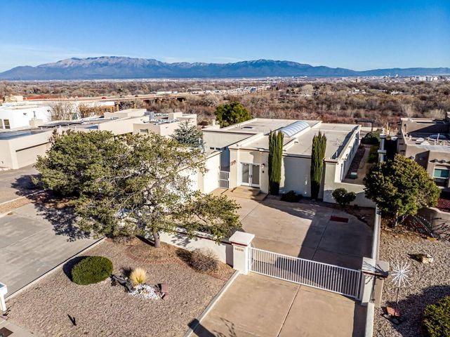 What an incredible, rare opportunity! Welcome to this sprawling single-story, riverfront home in the highly sought after Vista Magnifica neighborhood featuring inescapable, majestic views of the city and the Sandias. Upon crossing the threshold you'll notice how the natural light floods the exquisite hall/ entry way abounded with custom cabinetry, shelves and ledges. The regal fireplace mantle shimmers in the spacious living room that also features a wet-bar. Outstanding views and patio access from the large master and the master bath features double sinks, separate shower and large garden tub. The secondary bedroom also features patio access and it's own bathroom, perfect for in-law quarters!  Large kitchen with island, double ovens, bar area, and breakfast nook with phenomenal views!