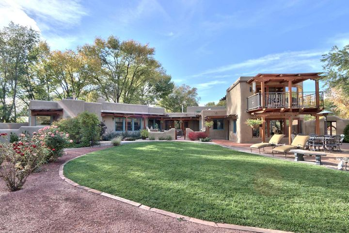 Gorgeous Taos-style adobe hacienda filled w/ light & character featuring expansive mountain views in a lush, park-like setting. Two luxurious master suites sit in opposite private wings. Updates include 3 refrigerated air combo units, walnut hardwood floors & refinished brick. Character abounds w/ viga & latilla ceilings, 4 kiva fireplaces, custom stained glass windows & hand-crafted chandeliers. Spacious gourmet kitchen boasts granite counter tops, 8-burner SS Jennair stove, large pantry, 14-foot ceilings & farm sink. Huge RV carport accommodates 40' vehicle w/ convenient 220-power. 3 car-finished garage has large storeroom & space for workshop.  Lush backyard is bursting w/ rose gardens & fruit trees, including cherry, apple, pear, peach & plum. Corrales country living at its finest!