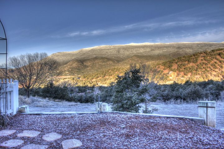 Enjoy nature and privacy in a serene location only 10 Minutes to Albuquerque! Majestic panoramic views of the Sandia Mountains from this stunning Northern New Mexico home. This property features an awesome 40 X 40  insulated, heated and cooled Workshop with 1/2 bath and RV door. Spacious 17 X 15 Master Suite with quality wood engineered floors, a gas log fireplace, exceptional master bath and grand master closet. The kitchen has granite counters and custom cabinets. Stay warm on those cold winter nights with an almost new high efficient pellet stove. Private  rear 20 X 11 covered patio. with access off the MBR and FR. Back yard is walled & has artificial turf. Huge loft area upstairs could be 4th bedroom, media room. exercise room or other possibilities, 2 spacious bedrooms upstairs and a