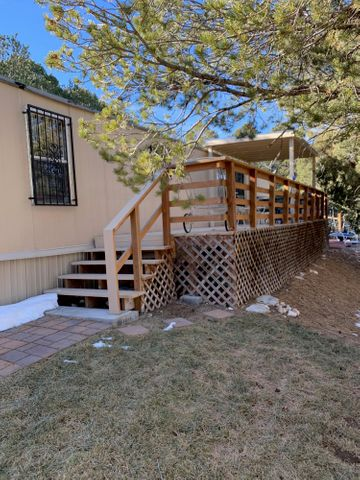 Move in Ready! This updated 2 bedroom 2 bath home with an oversized double carport is situated on 1.5 acres in a lovely mountain setting. Paved driveway and privacy entry gate and fencing surround the home. Includes a covered deck with steps down to a brick patio area.  I 40 is easily accessible for a quick 12 mile drive into Albuquerque or 6 miles to Edgewood. Make this home yours today. Cash or Owner Financing.