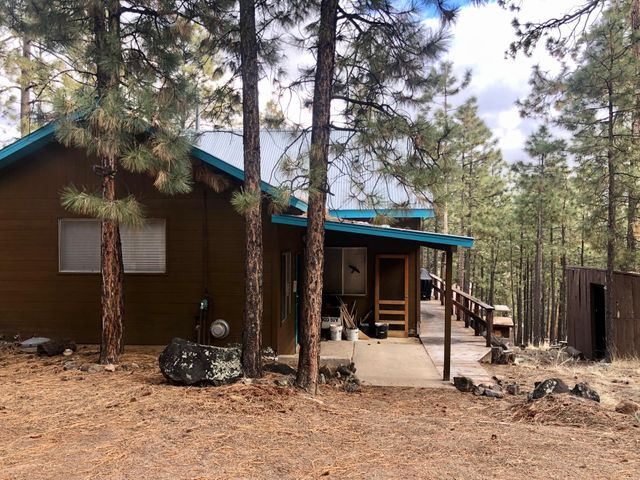 Just a sweet mountain cabin to get away from it all! Private setting with tall ponderosa pines. Large outdoor deck to barbecue and watch the deer. Spacious warm living area, complete with toasty woodstove. Recently remodeled kitchen with very nice appliances, flooring, cabinets, and counters. Sweet breakfast nook. Large dining area big enough for everyone. Wrap-around forest views to enjoy! Three good sized bedrooms and 2 upgraded baths, plus a large laundry room. Storage shed has both a storage room and a woodstove sauna!  All furnishings can stay; presently enough beds to sleep 10. Only drawback is older carpet, but seller assured me you can spill a whole bottle of red wine on it, and no one will ever notice. This could be fun!  Come see it soon!