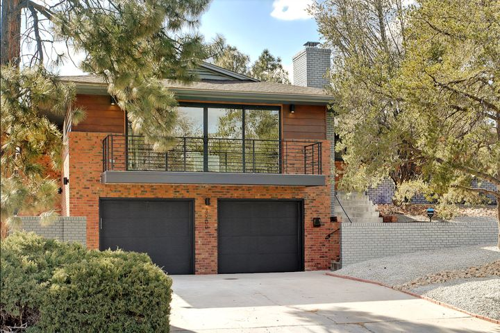 Enjoy this light filled Apex design property in UNM North! Extensively updated Mid Century, contemporary house has 3 fireplaces & 2 owner suites. You know you have entered a special home as soon as the wide pivot door opens, & you step onto the maple wood floors. Great room with living & dining rooms, has a center open sliding glass door, that opens to a balcony with expansive views. Kitchen has new maple lower, & white upper cabinets, quartz counters, subway tile backsplash, pantry, stainless steel appliances, wine fridge, a large eat at island, & fireplace. Kitchen opens to covered patio & grass backyard. Main owner's suite has double sinks, jet tub, barn door leading to a huge walk in closet. Lower level owner's suite has fireplace, large closet & separate entrance.  Refrigerated A/C.