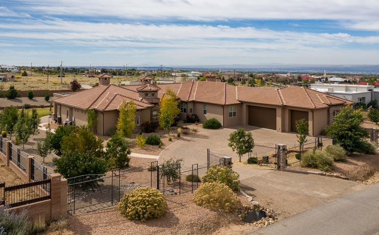 North Albuquerque Acres, Spacious Single Level (NO steps), Fully Gated & Landscaped! Superb layout= wing #1: MBR + Formal Office + Gym/Nursery/Bonus Room, centralized kitchen & living/entertaining spaces, wing#2: 2 sets of guest bedrooms each w/ jack & jill bathrooms + additional work space. Open kitchen w/ large island, gas cooktop, pot filler, range hood, under-mount lighting & pantry. Travertine & teak hardwood floors- NO carpet. MBR has exterior access, additional sitting room & 2-way FP. MBA had circular jetted tub, his/hers vanities, steam shower + walk-in closet. Excellent storage + garage w/ tall, insulated doors. Expansive back patio overlooks the lawn & several fruit trees, nice open patio spaces, plumbed for outdoor kitchen & extra exterior 1/2 bath. Schedule your showing today!