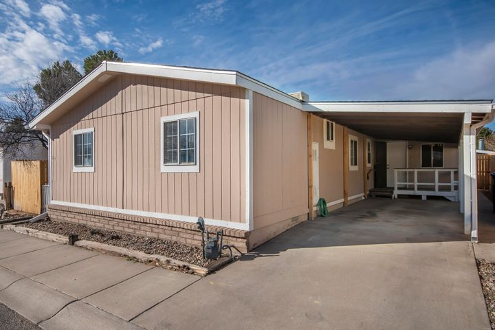 Come see this nicely maintained home in Sun North Estates Mobile Home Community!  Open floor plan offers spacious kitchen-living area w/ fireplace.  Roomy and bright owners ensuite; separate wing features 2 bedrooms and a bath.  Large laundry area w/ storage.  2nd living area addition w/ separate entrance, plus built-on workshop/storage/office, located off the owners suite (not heated).  Carport and private yards. Great location with easy access to I25.  La Cueva HS district!!  Recent flooring, paint, roof, and more.  Pleasant neighborhood with HOA clubhouse and pool.  A nice place to call home.