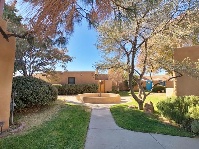 Open House Jan 26, 1-3p. Fabulous Hap Crawford-designed single-story adobe-built home in the North Valley's Cimino Compound. Unit #1 sits in a discreet corner of the community--nicely walkable to restaurants & shops, yet tucked away from Rio Grande Blvd. To reach the townhome, cross one of the numerous lush greenspaces that stretch across the complex, to the private high-walled courtyard entry, past the landscaped sitting area. Now come on in to high-volume T&G ceilings with viga beams,  beautiful patinaed red brick floors, a dramatic Kiva fireplace centerpiece with nicho, granite counters & stainless appliances, two bright skylights, new pendant lights, sconces & updated bath fixtures. You'll love the corner office nook & wall-length bedroom closet, too. Plus, pool & clubhouse gatherings.