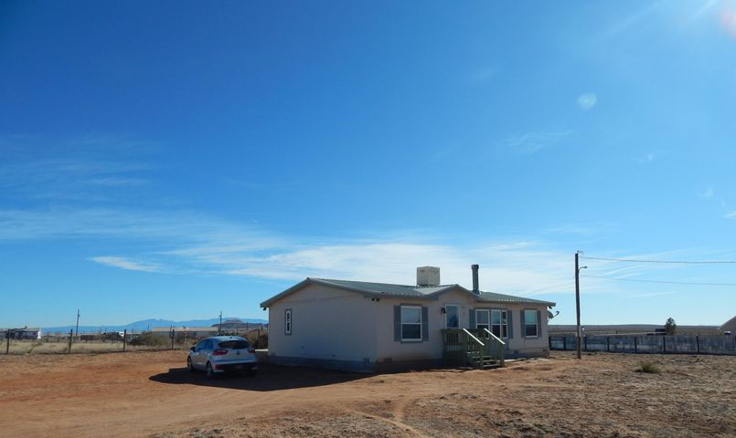 Get on board with the big Los Lunas boom!  Well maintained manufactured home on 1.67 acres completely fenced & cross fenced.  Dog kennel fence and east and west property fences are buried a foot under ground .  Floor plan is open & light and bright with 3 bedrooms and 2 full baths.  Living Room has a wood-burning fireplace for cozy nights.  Enjoy gorgeous mountain views from the deck.  Durable metal roof and horses are welcome!  Easy access to I-25 and Albuquerque!