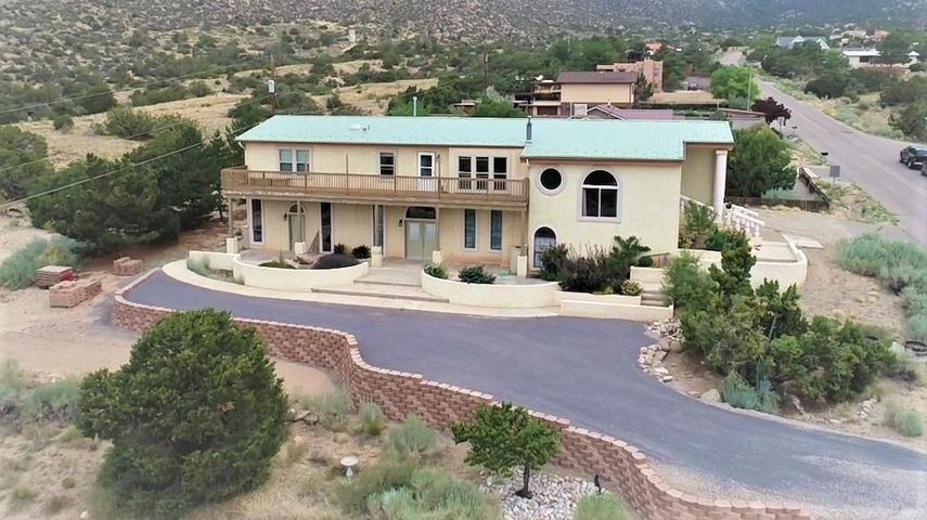 Take in the stunning views of the Manzano mountains as the sun rises and sets from the south facing windows of this immaculate two-story home. This 4 bedroom 4 bath home sits in the Canyon of Carnuel (still considered Albuquerque) just a couple of  minutes away from Albuquerque/Tramway. This multi-generational home has an abundance of space to relax or entertain. The two-car garage includes a large loft for storage and/or hobby space. Gives possibilities to be a potential income property as an AirB&B or rental. All appliances included except the downstairs fridge and freezer.