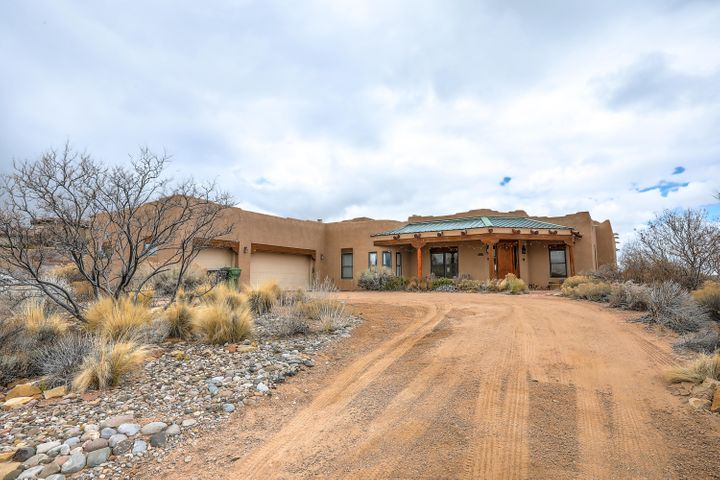 A gorgeous, custom built, one-level New Mexican style hacienda w lovely views awaits you.  You will instantly be charmed by the covered portal, vigas and natural light  Next you will appreciate the plaster walls, tongue-in-groove ceilings & rough-hewn timbers.  The great room features high ceilings w a lovely kiva fireplace, bancos & ceiling fans.  The kitchen boasts a large prep island, walk-in pantry, stainless steel appliances w a large range hood & a breakfast nook. You will love the four spacious bedrooms (two true masters!) w abundant storage.  Plus a bonus office w French doors & an additional sitting area. The grassy backyard features a large covered porch w see-forever views.  Watch the rain storms roll in!  So much to love about this home- come see it toda