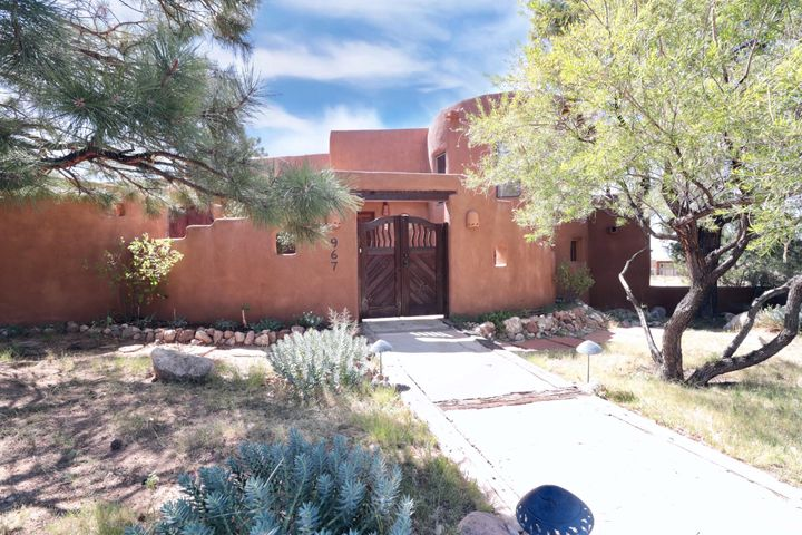 Gorgeous costume adobe home originally designed by the award winning local architecture firm of Max Flatow. Home has many unique features, its a Southwest/Santa Fe style beauty! Colonial Mexican tile floors, Venetian plaster walls, Kiva fireplaces, Wood vigas & latilla ceilings. Kitchen/dining are open and look down into the living room. Dining room features an authentic Taos Pueblo drum light fixture, custom cabinets, SS appliances, new gas stove, Corian solid surface counters & hand painted Mexican tile backsplash. New hickory wood floors in bdrms & Family rm. Master has viga & latilla ceilings, kiva fireplace. Master bath suite has walk-in cedar closet, steam shower, custom cabinets, travetine counters, travertine floors, custom towel racks. Laundry room is off the master bath.