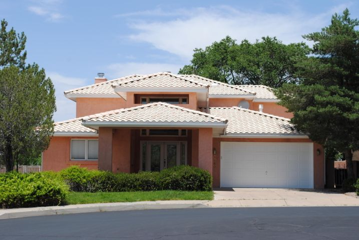 Classic Tanoan home on the golf course backing to the Sandia 9. Covered circle driveway. Double glass doors greet you and open to a grand staircase in the foyer where travertine tile floors await. Lower level bedrooms share a Jack n Jill bath. 3rd room with built-ins and wet bar can serve numerous purposes - Office, hobby or 4th bedroom. Step down living room with stone fireplace and handscraped hardwood flooring. Kitchen counters covered in granite including island counter with gas cooktop. Breakfast nook and formal dining room with built-in corner cabinets. Sunroom with more travertine completes the lower level. Entire upper level of the home is the master suite. Nicely arranged bedroom with bed platform also has a wet bar and plenty of room for