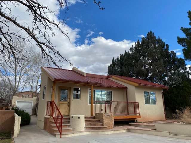 Great opportunity to own this custom home located walking distance to Nob Hill shops/restaurants; close to UNM.  NOT your basic two bedroom, one bath home.  Recent additions include extended front porch, an artful entry foyer with high ceiling, extended space to living room; windows and pitched metal roof; extended main bedroom with walk-in closet; new H20 heater; newer evaporative cooler (2 y.o.); flat roof portion of home (2017 foam/sealed).  Bright kitchen in rear of home with windowed eating area and back door to yard.  Most flooring is hardwood; some tile; partial basement w/laundry area (not incl. in sf); single car garage (access limited); gate access to alley.