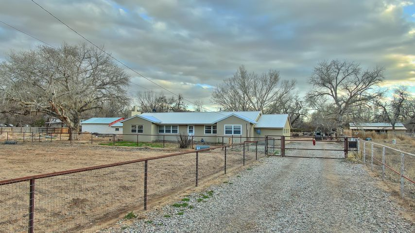 Location!  Eastside Corrales Road,  Southend location!  Fabulous horse property on 2.5 acres that is divided into two lots.  Paved road, gated entry, pipe fenced,  large metal 5 stall barn w/runs,  roping size arena, hay storage, lights, water, storage barn w/tack, separate northside pasture area, and set up for a true horseman or horsewoman!  South access to Gosset Lane.  Situated with Cottonwoods, the original home which needs update, remodel, or teardown to build your dream home in this great setting.Access to 688 acres of Bosque Preserve, riding trails,  or frequent the local restaurants or Galleries.  A must to consider and call home!