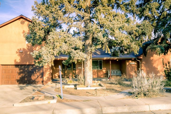 Just off the greenbelts in Ridgecrest! Roof & MasterCool new in 2019! Generously-sized home on oversized .25-acre lot with 2-car garage & full landscaping. Northern New Mexico farmhouse design with 4 bedrooms, 4 baths, 2 living areas, coved ceiling, FP & more. Kitchen has stainless-steel appliances & opens to dining room. Upper-level master suite has east-facing Trex deck with Sandia, Manzano &  Sangre de Cristo views! Two bedrooms & 2 baths on the main level incls a remodeled full bath. Add'l guest room + bath in basement. Recent paint. Recent vinyl floor laid over original hardwood. Double pane windows. Outside finds north-facing cov patio, fountain, fire pit, play area, cherry trees & backyard with sprinklers & bubblers. The location is close to Nob Hill, KAFB/VA & UNM!