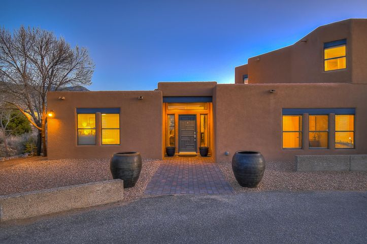 This magnificent custom home is set on a beautiful over 1/2 acre lot in the highly sought after community of Sandia Heights with striking 360 views of city lights, mountains, & painted sky sunsets. Perched in the foothills of the Sandia Mountains amidst the high desert landscapes.Immaculate home with numerous interior and exterior upgrades. This abundant 4 bedroom 3.5 bathroom home offers 3,369 SqFt of living space. Inviting interiors and wood style tile floors as well as many updates throughout command both functional flow & visual opulence. The grand kitchen is perfect for entertaining w/ unmatched views. Escape to your private upstairs quarters! A grand master en suite with jetted tub & separate shower, walk-in closets, balcony w/ impeccable views, private sun room, & spacious loft!