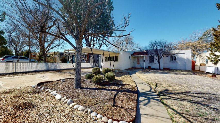 One Story Pueblo Style home in the heart of UNM South/Nob Hill offering 3 bedrooms, 1 full bath, & sunroom w/ 1128 SF. Original hardwood floors & saltillo tile can be found throughout the home. Living room has a quaint fireplace with mantle. Kitchen is open to dining room & offers plenty of cabinets & extra storage space.  Large laundry room has additional shelves & cabinets for storage.  Sunroom off of the laundry room has extra living space w/ plenty of sunshine.Converted one car garage serves as an additional living space or bedroom; your choice. Front door area is enclosed for extra security with iron bars and gate. Beautifully manicured front yard w/sprinkler system is fully fenced w/ a single carport. Walled backyard offers mature trees & flourishing landscape w/ storage shed.