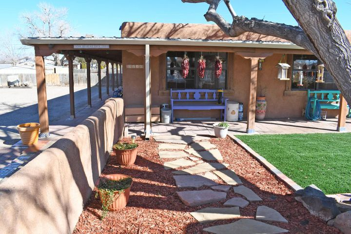 Stunning New Mexico Oasis! Beautifully landscaped Sante Fe style home situated on 0.32 acres. This 4 bed, 2 bath home boasts amazing entertainment spaces to include a large open kitchen with lots of cabinets, a family room with wood burning(insert) fireplace, tiled sunroom, and an outdoor family style patio! In-Law Suite.