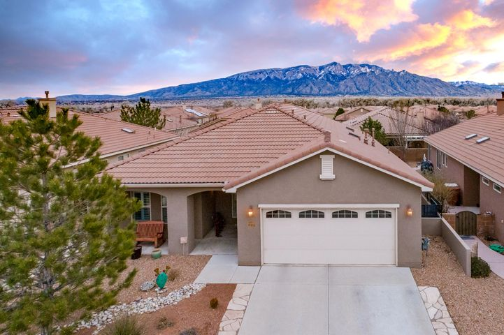 This stunning home has been meticulously maintained by the original owners.  Taos floor plan adorned with lovely upgrades.  Gourmet kitchen with granite counters, center island, pull out drawers in lower cabinets, walk-in pantry and wine frig. Beautiful plantation shutters, skip trowel finished walls, ceiling fans and surround sound. Master bedroom suite boasts custom designed closet, upgraded granite counters, double vessel sinks and linen closet. Dramatic sunroom with panoramic doors reveal gorgeous Sandia Mountain Views.  The floor to ceiling doors invite the outdoors in, allowing for optimal entertaining and pure relaxation! Extended patio, water feature, custom gate and flagstone walk to front.  This is retirement living at its finest.  Clubhouse, pools, walking trails & more!