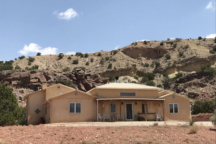 Quintessential New Mexico Hacienda on nearly 10 Acres with panoramic views of the Sandia & Jemez Mountains. This off-grid property has multiple buildings: furnished 2300+/-SF custom home, 450+/- SF yurt, 360+/- studio bldg. & 600 +/- SF steel pole shed w/roll up doors. The adobe style main home consists of 2 BR, 2.5 BA + office/library & is filled with natural light & 14' high ceilings w/exposed wooden beams. The great room has a custom highly efficient fireplace & French doors leading to a central courtyard.The kitchen has a wood fired oven & large island. The master bedroom suite has a custom fireplace & large walk-in closet.Multiple PV systems partner w/wind turbine. Reliable water system includes a deep well & storage tank. Off grid and located on a county road with a gated driveway.