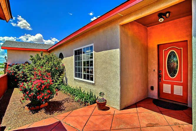 Beautiful Bernalillo home located down a private road with stunning views of the Sandia mountains! As you walk through the entry, you'll be immediately greeted by a large family room with vaulted ceilings and a cozy pellet stove. This room flows seamlessly into the cooks kitchen with a wrap around bar! Perfect for entertaining! Refrigerated air! 4 large bedrooms all with walk-in closets!  Master suite is located on the opposite wing away from the other 3 bedrooms and includes a sitting area, jacuzzi tub, dual sinks and separate shower. There's also an office that could be used as a 5th bedroom! Covered patio in the backyard with raised planter beds that are ready for your personal touch! Landscaped with roses, fruit trees and grapes! Detached 3rd garage space and room for your RV and toys!