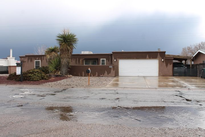 Great location to shopping and  Restraunts.  This home has been loved lots of updates Walk in Master shower and closets.  Backyard Access with beautiful VIEWS of the Sandia's... additional covered carport and plenty of parking space.  Corian countertops in kitchen tile and lamitnate flooring.