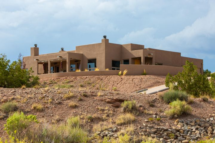 Amazing Sandia Mountain views from this single level - no steps! - custom home atop a 2.31 acre lot dotted with pinon & juniper. Built in 2014, the property is located in the La Mesa Subdivision of Placitas, only 3.5 miles to I25! 4 bedrooms, 2 1/2 baths and oversized 2 car garage. Custom touches include: chipped edge travertine flooring, 3 wood burning fireplaces, raised beamed ceilings, built-in lighted shelving, 2nd bedroom functions as media room - all equipment conveys! Gourmet kitchen features an island with breakfast bar, granite counters, tumbled and stacked stone backsplash, s/s appliances, gas stove w/ pot filler, walk in pantry, and soft close cabinets. Recently re-surfaced driveway. Community water & natural gas. Welcome home!