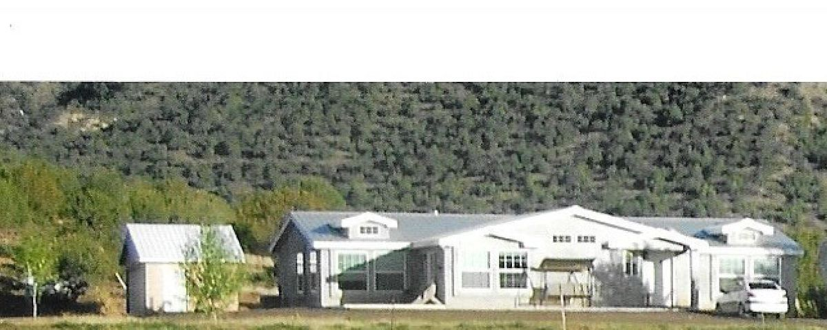 Located in the beautiful Jemez Mountains 45 min. from Albuquerque, this welcoming 3 bed/ 2 bath home w/ 360-degree mountain views is a turnkey equine/ranching facility. House is 2003 2,330 sq ft Karsten Home, enclosed in stucco on 8.95 acres.  Enormous living room w/ wood burning stove for chilly mountain evenings.  Big, bright kitchen features granite counter tops, island & stainless appliances.  Laminate wood floors and tile in wet areas Large master suite w/ generous walk-in closet & bath w/ double sinks, oversize shower & separate soaking tub. 2,676 sq ft barn features covered paddock, stalls, feed & equip storage & tack room w/ bar. 150' x 400' arena has roping/cattle chute w/ lead-up & stock return. Irrigated via private pond, deeded water rights allow 3.11 acre ft/yr.