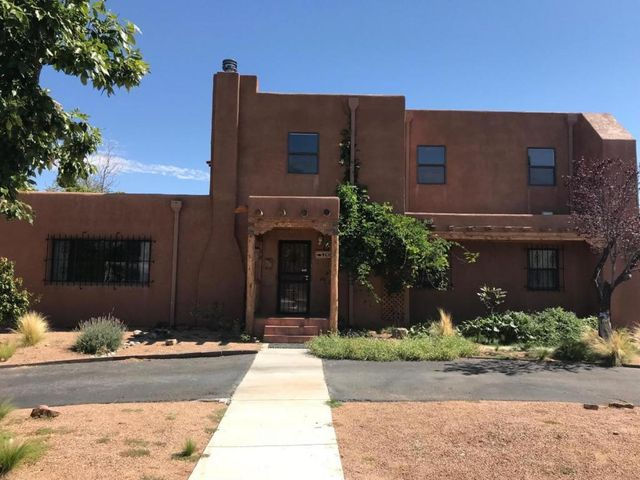 Charming Ridgecrest area pueblo-style home near Nob Hill, UNM, Kirtland, and Sandia Lab. Four large bedrooms downstairs (one could be office). Master suite upstairs with beautiful wood-beamed ceilings, living area, wood stove fireplace, walk-out to rooftop deck, huge master bedroom, master bath and walk-in closet. Original hardwood floors downstairs, cozy kiva fireplace, kitchen remodeled with granite countertops and high-end stainless steel appliances. Passive solar design with sun rooms upstairs and downstairs (not included in square footage). Owned solar panels, central heat/air and upgraded electrical service. New roofs installed on upper floor and shed in December 2018. Yards xeriscaped with raised beds and drip irrigation. Large, 2-room storage building (could be studio/ man cave!).