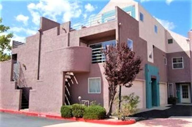 Beautiful ground level condo in the base of Sandia mountain. Contemporary SW style with hardwood floors, no carpet. Open floor plan. Ref. Air, Large master bedroom with patio door leading out to beautiful twinkle city light view. Some SS appliances and washer dryer stay. Community offers Pool And Clubhouse. Hiking & biking trails are only steps away.