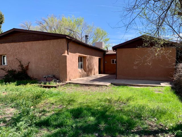 Large adobe block home on 1/2 acre w/ great big solid storage/workshop/barn >>2000sf +/- on property; was once used as a warehouse for local farmers. Home has had some recent updates to include: large bathroom w/ tub, tile, shower, sink, updated small bathroom w/ sink and flooring, laminate flooring in all bedrooms, painted walls in living room, kitchen, bedrooms, hallway, insulated windows on North side of house, concrete patio. Updates within 10 years includes: furnace and swamp cooler, updated main water connection and water lines, and stucco. Great opportunity for use as investment rental or as local *mini farmers market - sell community grown fruits/veggies/ fresh eggs etc. right off Isleta! Dollar store across street. *A-1 Zoned. Ditch rights.