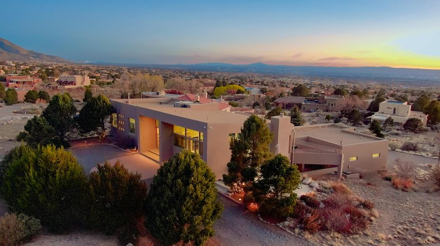 The Ultimate Revival / Rebuild!! Completely rebuilt main two level home by Lewton Construction in 2008! Tremendous lower level addition by Dura-West in 2012! Combined this has created an absolutely magnificent home with outstanding mountain/city orientation and the best views possible. Huge attention to detail with exceptional finishes and luxurious lighting throughout this one of a kind contemporary southwest custom home. FULL property description available. Multiple living and dining areas feature floor to ceiling glass for magnificent Rio Grande valley and Sandia Peak vistas. Two decks and three patios provide incredible outdoor living areas- each with equally breathtaking views. This is a rare find - see it now!