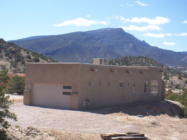 NEW 3 BEDROOM WITH VIEWS OF SANDIAS & CABEZON! Brand new, custom, pueblo style home with lots of natural light, exposed beams, spacious kitchen, great room/dining room combo, huge windows & 2 full baths. 1850 sq ft + 2 car (finished) garage on 1 acre with outstanding views of mountains & sunsets! The kitchen is open to the great room & includes granite counters, island, pantry, breakfast bar, soft close cabinet drawers/doors & VIEWS!. Beautiful 20'' tile in much of the house. Gas fireplace in great rm. Master bath has separate shower, oversize tub , double sinks & walk-in closet. Refrigerated air! Reasonable covenants, but no HOA. Kitchen appliances are included and the builder is planning on carpet in all the bedrooms. Home to be finished in April! (Photos will continue to be updated...)