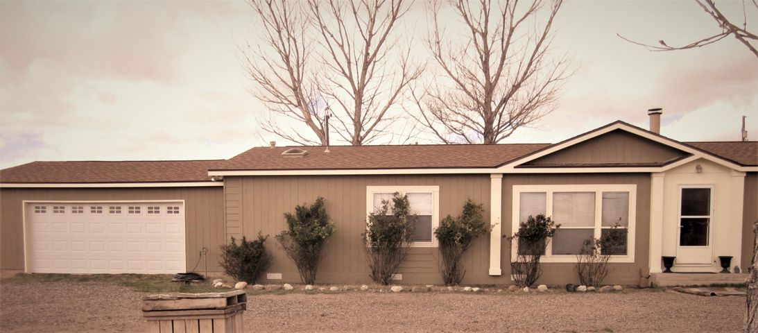 Charming, updated double wide with double garage, stable w/workshop, and large paddock on 1.53 acres. Quiet country atmosphere with mountain views right off of Hwy. 116, about 4.2 miles south of Belen. Was inspected for a VA loan 5 years ago and drainage, foundation, well and septic approved. With 3 bedrooms,2 full baths, country kitchen with island, pantry bar and modern appliances, there is all you need for a place to bring your horses/other livestock or to just sit back and relax. Owner has done upgrades in professional painting and new flooring in much of the house. There is a cozy FP and views from the living room to the mountains. Owner has added an enclosed patio, perfect for barbecues or entertaining - or your hot tub! If you need more acreage, the vacant lot to the E is for sale.