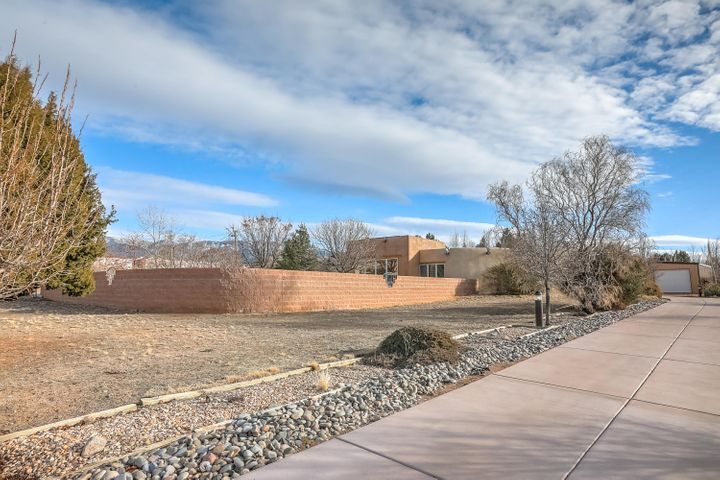 Welcome to this beautiful custom one story Adobe home in NAA w/stunning views of the Sandia Mtns. Southwest ambiance & luxurious appts include Marmorino plastered walls, brick floors, beam & knotty pine ceilings, Pella windows & exposed abode walls. Foyer sitting rm, spacious living area w/wood burning stove, wet bar & picturesque windows. Updated cooks kitchen w/granite ctps, breakfast bar, hickory cabinets, Kiva fireplace & stainless steel appliances. Master suite w/2 walk-in closets, lg updated shower, soaking jetted tub. 2nd Master suite with 3/4 updated bath, Kiva f/p & walk-in closet plus roomy 3rd bedroom & hall full bath. Outdoor living includes a large covered patio, gated heated pool w/cover, 2.5 attached garage + Oversized 2CG/workshop, storage & solar panels & more!