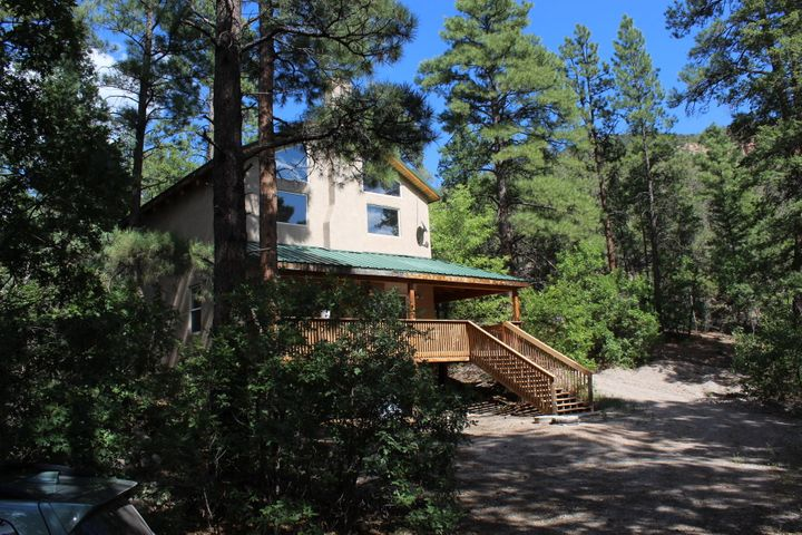 Now here is a listing to see and HEAR!! Nestled right down along the Jemez River. With OVER 300 FEET of RIVER FRONTAGE the sound of the river will ABSOLUTELY become a delightful part of every day and every night!! Spacious open living area has floor to ceiling windows and 2 sets of sliders to the covered composite deck. Well arranged, efficient kitchen has a great eat-at bar. Good-sized bedroom, Office and full bath on lower level. Upper level is HUGE master with comfy sitting area, full-bath & large walk-in closet. Loft is a fun den/rec room, work/office or craft area. 1.1 acre lot is nicely forested with trails and plenty of hammock and gazebo spots! City water and county maintained road. There aren't too many available with this kind of amazing river frontage!! Get it TODAY!!