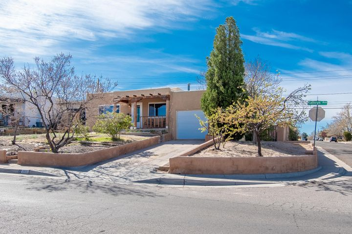 Charming mid-century home in UNM South area is close to airport, I-25, KAFB, CNM & UNM. This home has 3 bd/1 bth. Original wood floors throughout the home with tile in the kitchen, bathroom and large den. Ungraded kitchen with stainless steel appliances, separate dining area, new energy efficient windows, upgraded electrical panel 2016, home converted to refrigerated AC/heat combo 2016. Faux wood blinds throughout the home. Wood burning fireplace in living room. Lots of built in storage. Large den with 2 book shelve from floor to ceiling  and a plenty of storage cabinets. There is a drive way in the front and backyard. Storage shed in back yard stays.  Small storage space in front part of garage that was not converted to family room. New TPO roof 2019.