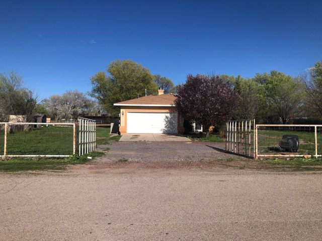 Inviting horse property nestled on just over a full acre. This fabulous 1 story home is in a great area of Los Lunas and within walking distance to Valencia Elementary School. It features a desirable open/bright floorplan with updated hard surface flooring throughout. Extras include horse stables and a gated horse arena, 2 living areas, gas fireplace, storage, covered patio and an attached 2 car garage. This amazing country property is fully fenced and has plenty of room... bring your family, horses, chickens, & animals and come make it your own today!!