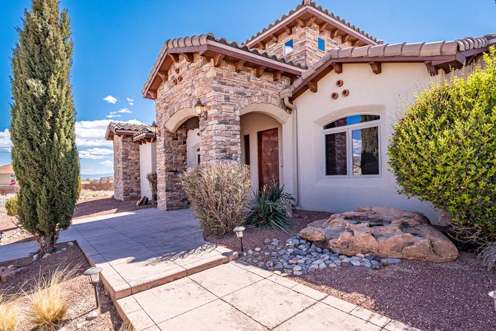 Amazing Custom Tuscany Style Home in Rio Rancho ! It starts when you enter though the most BEAUTIFUL CUSTOM Door and walk into an 18 ft high Foyer with TRAVERTINE  Flooring with CUSTOM Accent! BARREL Ceiling takes you into the Master Bedroom with a  SNAIL SHOWER /CUSTOM Closets, Double Drop Ceiling , Instant Hot Water Return, Dbl Sinks with a separate tub and shower. Kitchen has  GRANITE Counter Tops, JENN AIR APPLIANCES, Sliding Microwave and open concept with lots of cabinets and a pantry. Large laundry room w/ deep sink that leads into a large over sized garage with 8 FT Garage doors W Lift Master Openers. This home sits on .87 Acres. Landscaping Front and Back with Irrigation System. This home has so much to offer!  Horses Ok.