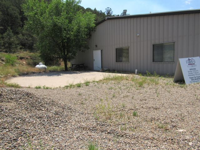 Turn this property into the home of your dreams. The building was originally built as a church building, but is zoned A-2 so can be used as a residence. Conveniently located on Hwy 14, just a short commute from Albuquerque.  Private well with storage tank; Upgraded septic in 2014; Refrigerated Air; Tankless water heater; Metal building can be customized to meet your specifications. RV Connections on property; Shipping container storage stays with property. Priced to sell!