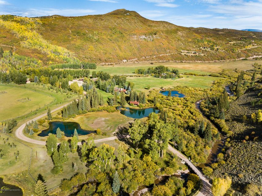 The dream of mountain living comes alive at this sanctuary in the Snowmass Creek Valley; a classic ranch with two homes, a five stall barn with caretakers quarters, paddocks and flat pasture land. Property has water rights with Snowmass Creek running right through it. Two separate parcels on over 75 acres includes a 3 bedroom home on each parcel. One parcel has an Austrian alpine cottage built as a tribute to the late, great Freidl Pfeifer. No detail or expense was overlooked and it is completely authentic in every aspect. It must be seen to be appreciated. The second home is a classic square log ranch style designed by Poss Architects. It features an open living room and kitchen complimented by a large wood burning fireplace, sure to be a favorite gathering spot on winter nights. Each bedroom feels private and warm with views looking out at the Snowmass Creek Valley. Step outside and walk the vast manicured lawn to the gazebo overlooking the trout ponds which will be the focus of many family gatherings and a lifetime of memories.