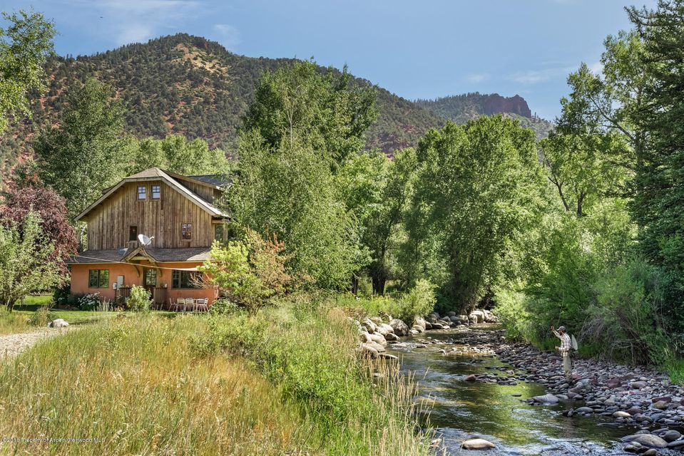 OWN YOUR OWN ISLAND ON THE ROARING FORK! Fish off your deck while taking in the amazing views of the river and surrounding mountains! This is the perfect property for your quintessential Colorado experience! The house sits on 2 acres of river frontage, which creates the ideal sanctuary. Only a short drive to Aspen or Snowmass for skiing and other activities The house boasts vaulted ceilings in the living room, a large second story deck, a patio level with the river, and tons of natural light throughout. The upstairs master bedroom is on its own floor with a separate loft overlooking the living room. There is a master suite on the main living level with views overlooking the river with an en-suite bathroom.