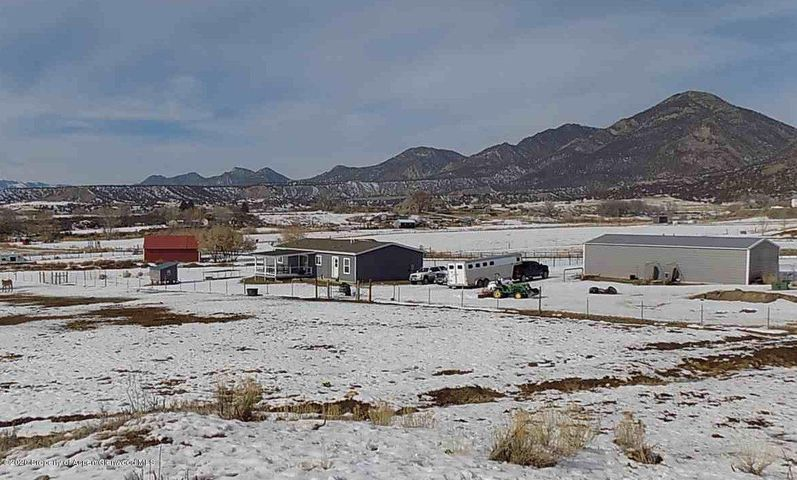 SILT MESA, 10 ACRE RANCHETTE!3BR, 2 BTH home, 30x50 shop bldg with concrete floor, 30x40 pole barn with insulated & wired tack or tool room, arena area, fencing and 5 shares of Farmers Irrigation water. NO Covenants. Home is a UBC/IRC/IBC modular on a heated, insulated crawl space, can be financed just as any stick built home.  Excellent condition, forced air heating,  central air conditioning with bright, open floor plan, large master bedroom and bath, stainless kitchen appliances and a 16x16 covered back deck area.  Property is fenced for horses with horse shelters in place. Beautiful views in all directions and great sunshine!  Access to BLM land from property.  Property has its own well and 350 gal storage tank and water softener. Owners do not need haul water.